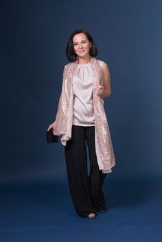 Elegant evening look in palazzo trousers, silky top and a sequined scarf