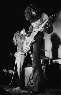 English guitarist Jimmy Page using a violin bow on his guitar during a performance with Led Zeppelin at the Empire Pool, Wembley, London, 23rd November 1971. On the left is singer Robert Plant. (Photo by Michael Putland/Getty Images)
