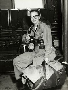 "Dickey Chapelle is seated on the USS ""Boxer"" with cameras around her neck and luggage at her side.   Wisconsin Historical Society"