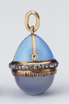 Easter egg pendant, 1903, top half blue enamel with four white enamel strips bordered in gold forming four panels; base of gold-mounted cabochon moonstone, rose diamonds encircling centre. Gold hanging loop. Mark of Michael Perkhin; gold mark of 56 zolotniks.