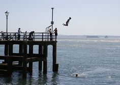 A woman jumps off the pier today in Portsmouth, Hampshire, during what has been the hottest day of the year so far in the UK