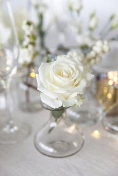 En rose i små glassvaser.