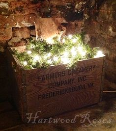 Farmers Creamery crate with artificial greens and a string of lights.