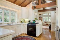 Easy, breezy, all white cottage kitchen with exposed beam ceiling at a newly renovated cottage in Carmel By The Sea.