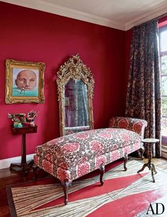 In a New York apartment, the room is painted in a Farrow & Ball red and features a cabriole-legged chaise longue.