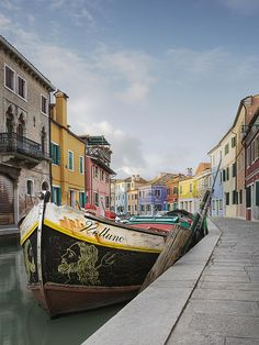 ✯ Boat in a Canal Lined With Colorful Homes