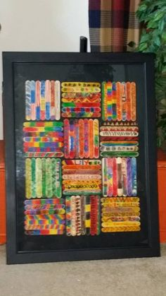 Gave my second graders each 4 sticks to color with markers. I got the frame at thrift and spray painted the cardboard background black to match. It came with the glass. (Someone had felt the need to preserve a jigsaw puzzle.) I hot glued the sticks (tongue depressor size) right to the backing.