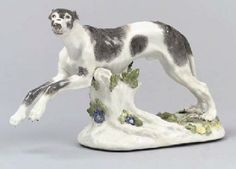 A MEISSEN MODEL OF A GREYHOUND CIRCA 1750, BLUE CROSSED SWORDS MARK AT BACK Modelled by J.J. Kändler, in running pose supported by a tree-stump, painted with grey-brown patches, the rocky base applied with flowers and leaves