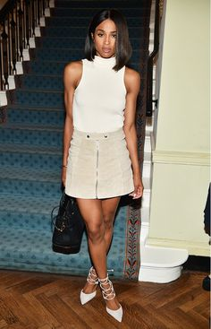 Ciara wears a high-neck tank top, zip-up miniskirt, and lace-up pointed-toe heels