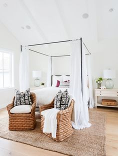 White walls, white bedding, black bed frame with white curtains, tan woven chairs, black and white printed throw pillows, tan woven rug, and cream nightstand