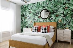 This guest bedroom, designed by Mollie Openshaw, has a tropical print wallpaper, creating an eye-catching accent wall for this fun space.