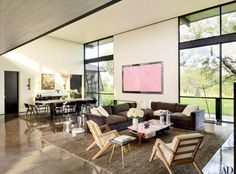 A painting by Andro Wekua hangs between the windows in the living/dining room; the bespoke rug in the seating area is by Carini Lang | archdigest.com