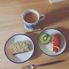 Breakfast with a slice of banana bread, fruits, and a cup of milk tea
