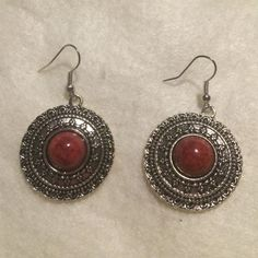 Gorgeous Tibetan Earrings These one of a kind earrings are brand new. They have never been warn. They are about the size of a quarter. They have a very pretty design around the entire earring, which helps the red stones to stand out. Jewelry Earrings