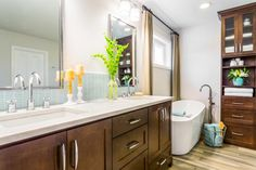 This master bathroom features a custom double vanity in a rich brown finish. Curtains soften the corner while creating privacy and framing the soaking tub. A tall, slender linen cabinet, which matches the vanity, provides ample storage without taking up much floor space.