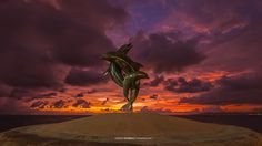 Fire In The Sky by Javier Moreno - picture of a terrific sunset over Banderas Bay along Vallarta's malecon showcasing the Friendship Fountain/La Fuente de la Amistad. Santa Barbara, California sculptor James Bottoms presented this fountain with its 3 entwined dolphins as a gift to the city in 1987, and it has been on the Malecon ever since.  More info on gay Puerto Vallarta www.discoveryvallarta.com/   #gay #travel #vacation #sunset #nature  #mexico