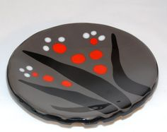 This striking fused glass bowl boasts a simple yet powerful design of black, red, and white on a background of medium gray. The back of the bowl was kiln-carved, so that the back is as interesting as the front. The bowl measures 8 in diameter. Small bump-ons are affixed to the bottom of the bowl to ensure it sits flatly on any surface.    This bowl can be used for serving, but its also a beautiful piece to add to any home decor. Hand-washing is highly recommended. Not intended for oven or…