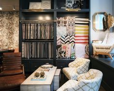 Retail Store Design Modern Photo - Rug and fabric samples on display behind a pair of armchairs