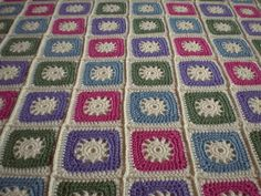 Crocheted blanket made of squares named Cogs, designed by Frankie Brown. Free pattern  download via Ravelry.
