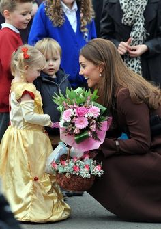A pregnant Duchess of Cambridge talks with children during a visit to Grimsby, England in March 2013.