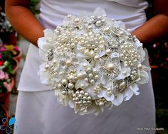 This artificial hydrangea and brooch bouquet features ivory hydrangeas, adorned with dozens of beautiful, high quality pearl brooches and swarovski