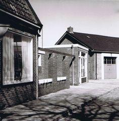 Zijkant van ons woonhuis en de achteringang van de winkel met op de achtergrond de oude brandweergarage met geeemteopslag.