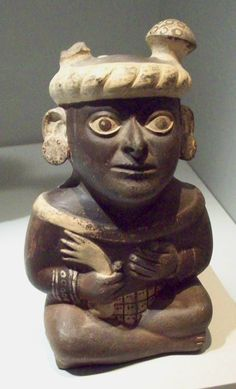 Pre-Columbian ceramic Moche portrait vessel wearing headdress with Amanita muscaria mushrooms, Peru. The Moche culture reigned on the north coast of Peru during the years 100–600 CE.