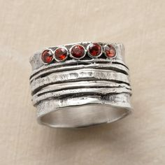 "CINQ RING -- Five garnets sparkle atop five variegated bands of hand-hammered sterling silver, making beautiful harmony. Whole sizes 6 to 10. 1/2""W."