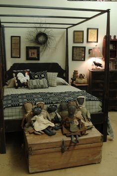 Primitive Bedroom...four poster, old dolls on the trunk, samplers on the wall & blend of textiles.