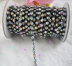 SAVE 10% when you spend $50 or more. Use Coupon Code SAVE10ON50.     1 yard (3 feet) SS18 (4.3mm) crystal AB rhinestone chain, silver. Excellent for collage, embellishment, sewing trim.    This rhinestone chain is very versatile! I use it to frame cameos on my embellished bracelets. I have also cut the linkage between the rhinestones when I need individual set crystals. They give a perfect finished look. to your project.