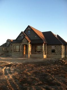 Stone and stucco Texas Hill Country home with metal roof accent