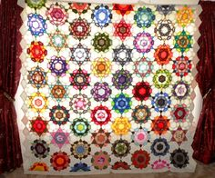 Rose Star Quilt hanging over the curtain rod with daylight behind
