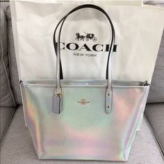 """NWT COACH Hologram City Zip Tote Stunning silver iridescent calf hair leather, silver changes colors on different angles and light. Limited Edition bag sold out in stores and online! Inside features cell phone, zipper and multi-function pockets. Dark brown fabric lining. 9 1/2"""" handle drop. PRICE FIRM. Coach Bags Totes"""