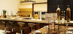 Salão de festas sofisticado em tons off-white, decoração com taças, cristais e vasos bronze. Banquetas em fibra e acrílico fazendo composição, churrasqueira pastilhada