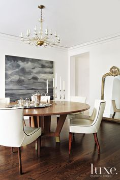 This round dining room table was designed by homeowner/interior designer Kazuko Hoshino while the mirror is a hand-carved French gesso mirror.