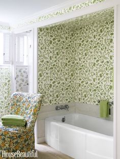 Designer Kathryn M. Ireland's Greta wallpaper in Reverse Green adds charm to a guest bath in a Cape Cod getaway. The slipper chair is covered in her Roses linen in Red.Click through for more bathroom designs.