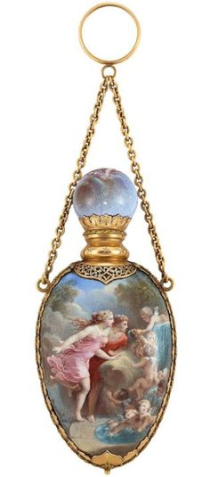 Gold and Enamel Scent Bottle with Gold Carrying Chain The modified oval bottle applied with enamel on both sides depicting garden scenes with female figures and playful cherubs, edged by stylized gold petals surmounted by a line of gold leaves and florets, topped by a light blue enamel ball with similar decoration and pierced gold scrollwork, circa 1880-1900.