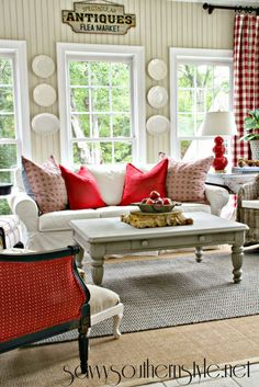Love the red accents,antiques sign and curtains in this beautiful Sun Room.