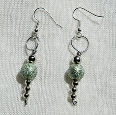These earrings shimmer and glisten in the light! This is a pair of wire-wrapped earrings that feature a couple green beads and a few smaller silver beads.