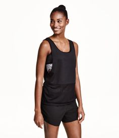 Loose-fit sports tank top in fast-drying functional fabric with sports bra built in. Low-cut neckline at back joined by strap at upper back. Deep armholes. Mesh trim at hem. | H&M Sport