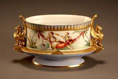 <b>Pirkenhammer Porcelain Moorish Revival Jardinière</b> <br /> <i>Fischer & Mieg, Third Quarter 19th Century</i> <br /> The oval body polychrome decorated with a woman smoking a hookah flanked by gilt-decorated griffins. Underside impressed with factory mark. <i>Restoration to rim; some minor wear to gilding.</i> <br /> <i>Height: 8 in (20.3 cm); Length: 14 in (35.6 cm)</i>