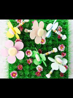 Dit heb je nodig: - lolly's - Snoepkettingen - Tumtum - Gekleurd papier - Schaar  Zo maak je het: Knip bloemen uit het papier. Steek de lolly door het midden van de bloem. Rijg de kraaltjes van de snoepketting aan het stokje van de lolly. Sluit af met een tumtummetje.