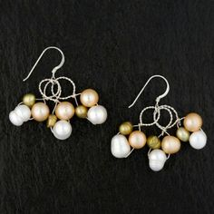a cluster of white, peach, and gold freshwater         pearls on sterling silver wire.