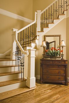This contemporary staircase has light oak treads and white railings with black iron spindles. An antique low dresser acts as storage in the place of a closet, and the rich dark wood provides excellent contrast to the oak floors.