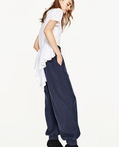 calças balão azuis camisa justa branca tacões pretos
