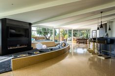 Sunken Media Room, Terrazzo flooring, bar with pendants, and contemporary dining table beyond