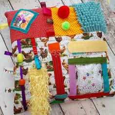 Ladies or Gents Activity Cushion Ideal for anyone with a brain injury, dementia or fidgety fingers! Will also aid in keeping the mind active! You will receive the cushion shown which has.....different textured fabrics, bright colours, beads, buttons, zip, hook and loop, ribbon