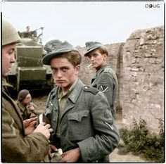 7th of June 1944. Near Saint-Gabriel-Brécy, Calvados, Lower Normandy, France. Two young German POWs are searched after being captured by British troops during the Battle of Normandy.