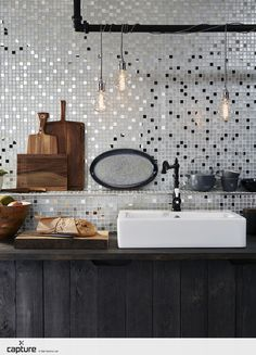 A great take on the industrial trend with metallic mosaic tiles contrasting against the rustic textured woods. Bespoke kitchen units with rustic chopping boards, pendant filament bulbs hang off the black pipe work. Photography by http://capture.setvisions.co.uk/Portfolio