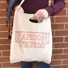 Everyone loves Netflixs newest show - Stranger Things. Thats why we made this tote inspired by the shows opening credits. Perfectly large for carrying around all your necessary yet random things.  Graphic is red heat-press vinyl. Machine washable.  16.5 x 15.5 American Apparel bull denim woven cotton tote (read: super durable)  Convo to get pricing on shipping outside of North America…